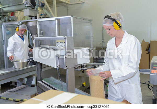 Two people working on factory production line - csp33127064