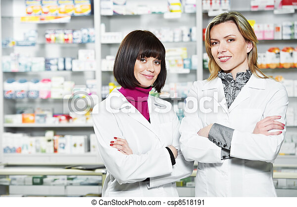 Two Pharmacy chemist women in drugstore - csp8518191