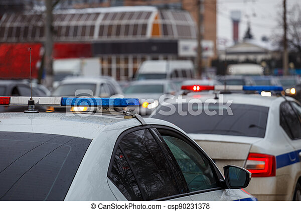 two police cars lights in city street at winter day with cars traffic in blurry background - csp90231378