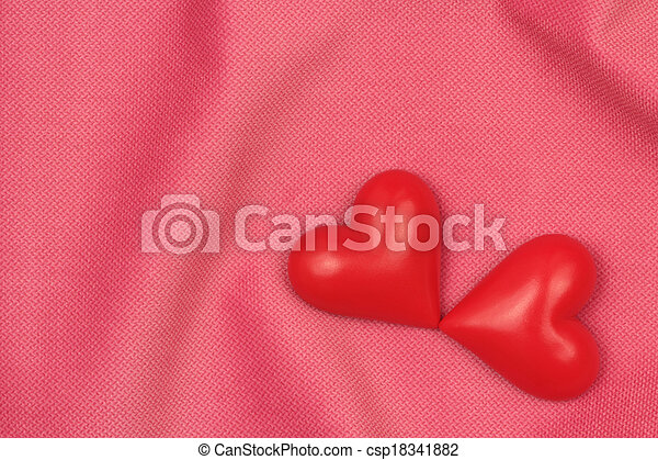 Two red hearts on a pink fabric background - csp18341882