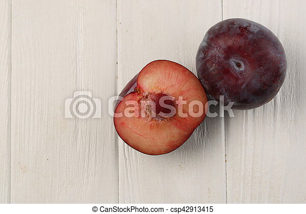 Two ripe plums on the table. White background - csp42913415