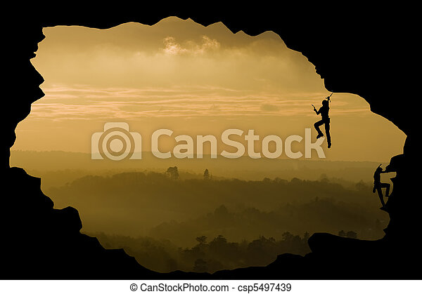Two rock climbers silhouette against stunning sunset landscape c - csp5497439