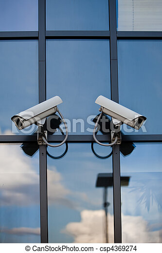 Two security cameras attached on business building with reflections  - csp4369274