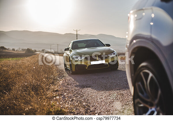 Two sedan cars parking on the road - csp79977734