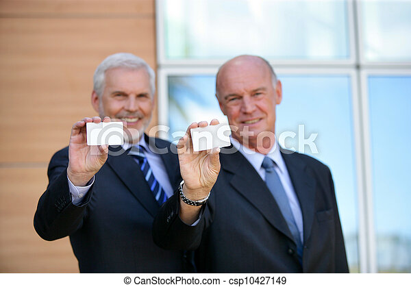 Two senior businessmen showing cards - csp10427149