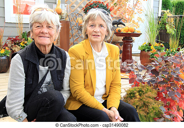 Two senior ladies seated on a patio - csp31490082