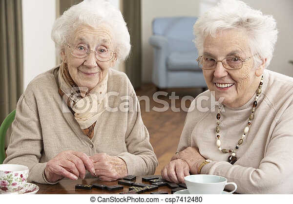 Two Senior Women Playing Dominoes At Day Care Centre - csp7412480