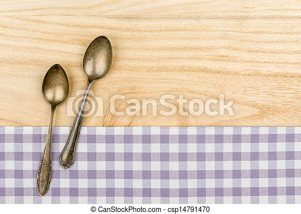 Two silver spoons on a purple checkered table cloth on a wooden background - csp14791470