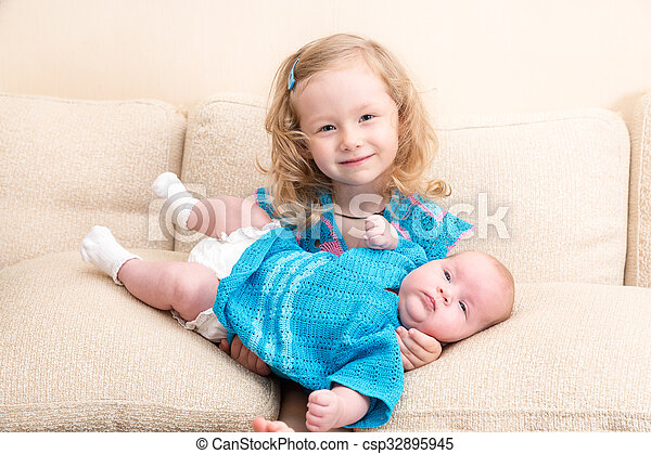 9b528a0438412 Two sisters. Older sister kid hugging his newborn little sister. Cute  children girls lying on bed at home.