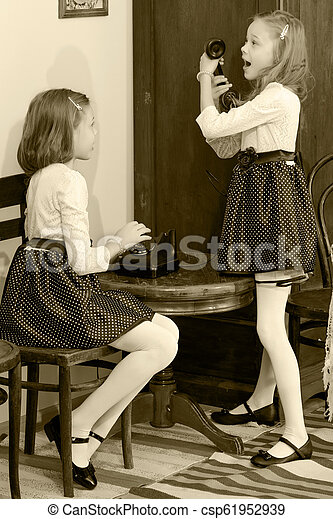 Two sisters talking on old phone - csp61952939