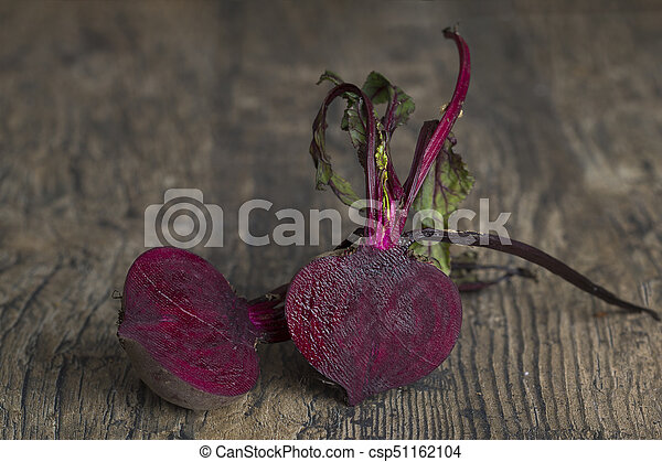 Two sliced beetroot on a brown wooden table in artistic conversion - csp51162104