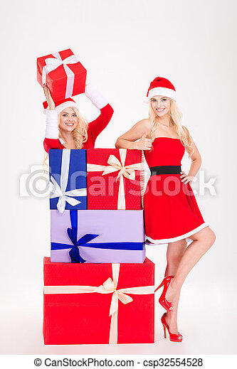 Two smiling woman in santa cloth standing with present boxes - csp32554528