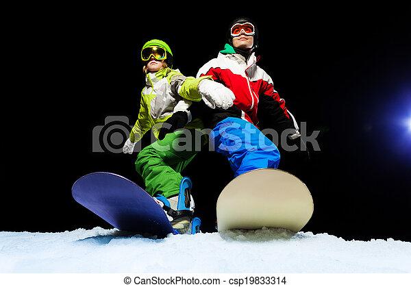Two snowboarders wearing ski mask at night - csp19833314