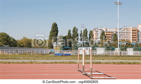 Two Male Sprinters Jumping Over The Hurdle At Stadium Young Sportsmen Competing In Hurdling Side View Of Fit Guys