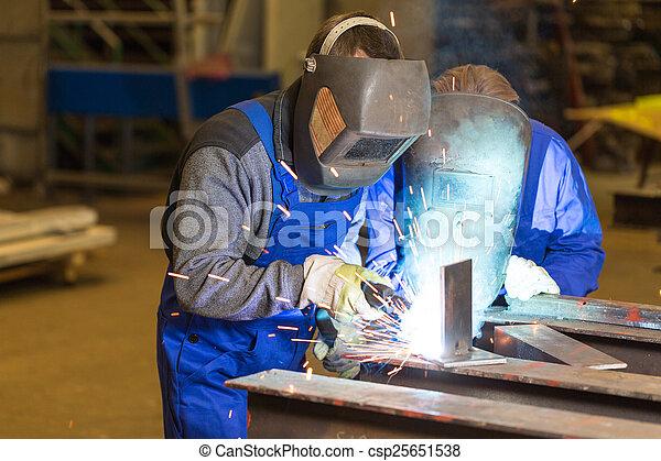 Two steel construction workers welding metal - csp25651538
