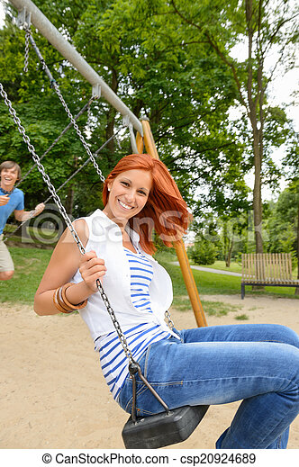 Two teenagers sitting swing in park playground - csp20924689