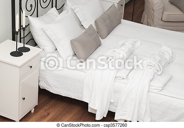 Two terry white dressing gowns on a bed in a bedroom.