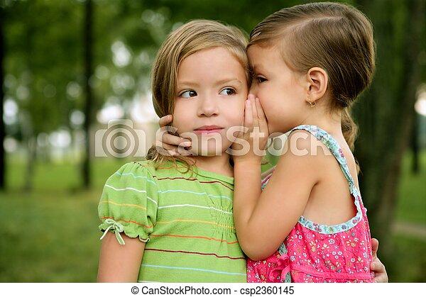 Two twin little sister girls whisper in ear - csp2360145