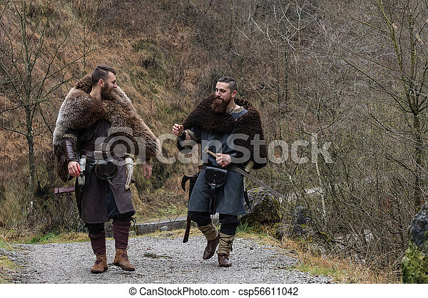 Two Viking Warriors Walk On An Ancient Forest Path