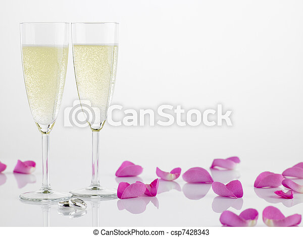 Two Wedding Rings Next To Champagne Flutes And Rose Petals - csp7428343