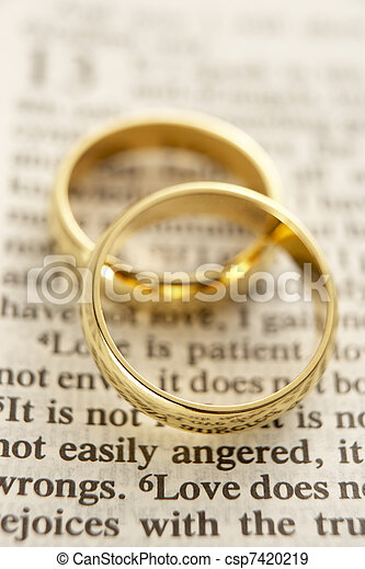 Two wedding rings resting on a bible page stock photographs