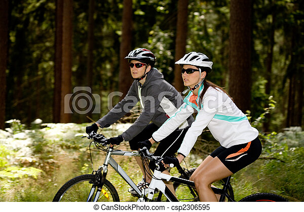 two women cycling in the forest - csp2306595