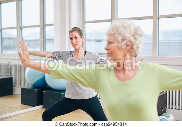 Two women doing stretching and aerobics workout - csp24954314