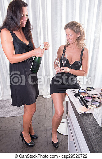 two women having a bottle of champagne - csp29526722