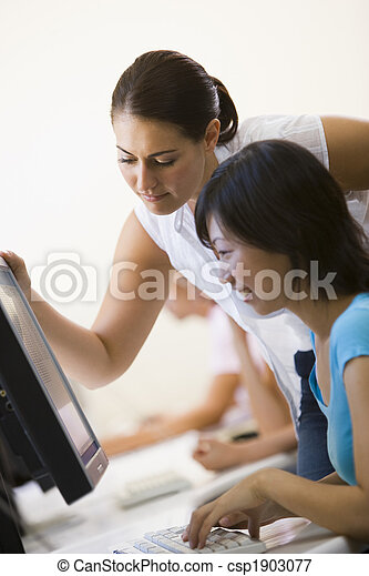 Two women in computer room where one is assisting the other - csp1903077