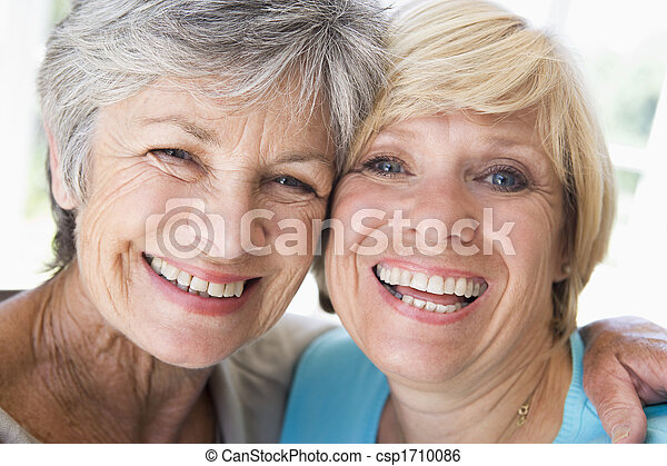 Two women in living room smiling - csp1710086