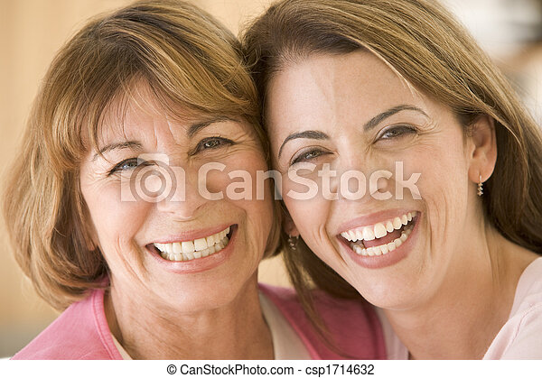 Two women in living room smiling - csp1714632