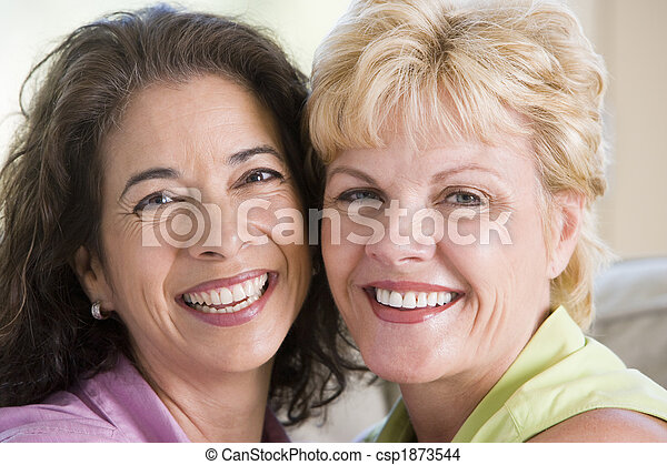 Two women in living room smiling - csp1873544