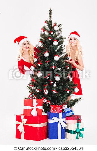Two women in santa cloth standing near christmas - csp32554564