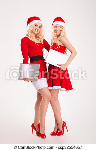 Two women in santa cloth standing with laptop computers - csp32554657