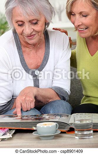 Two women looking through family photo album - csp8901409