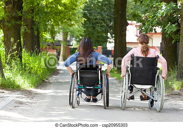 Two women on wheelchairs in park - csp20955303