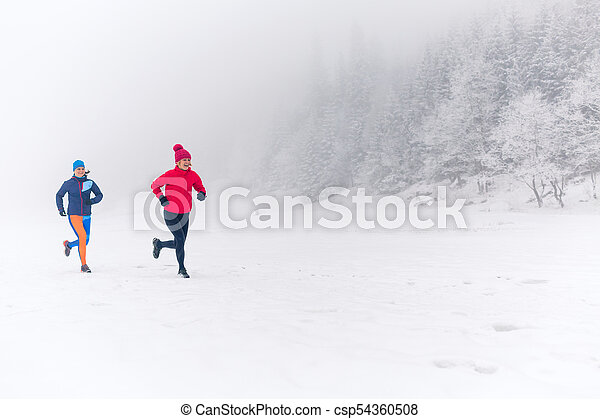Two women trail running on snow in winter mountains. Girls running together  on snow in winter mountains. sport, fitness | CanStock