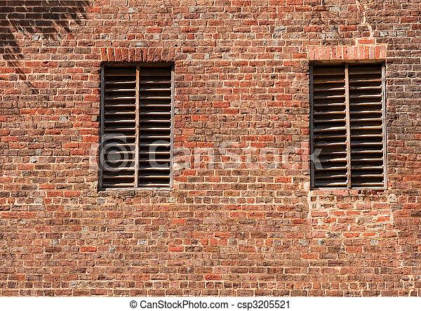 Two Wood Slat Windows on Old Brick Wall - csp3205521