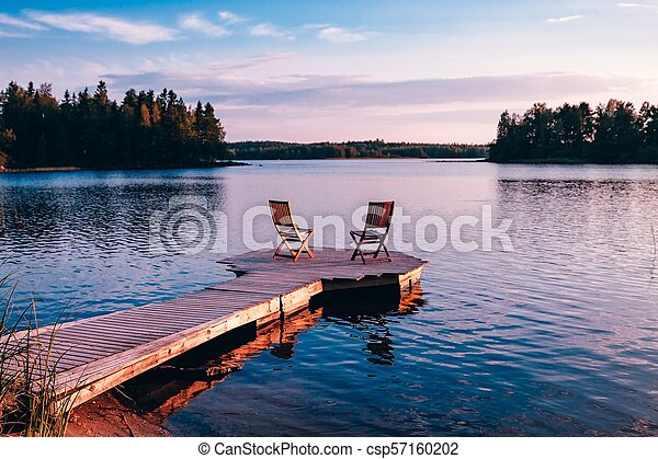 Two wooden chairs on a wood pier overlooking a lake at sunset - csp57160202