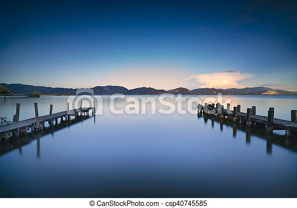 Two Wooden pier or jetty and on a blue lake sunset and sky reflection on water. Versilia Tuscany, Italy - csp40745585