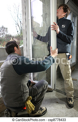 Two workers fitting window - csp8778433