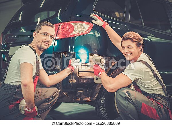 Two workers with colour samples choosing correct tone in a car body workshop  - csp20885889