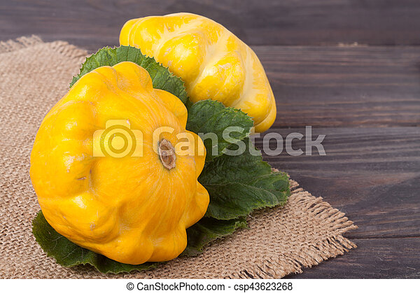 two yellow squash on a wooden background with napkin of burlap - csp43623268