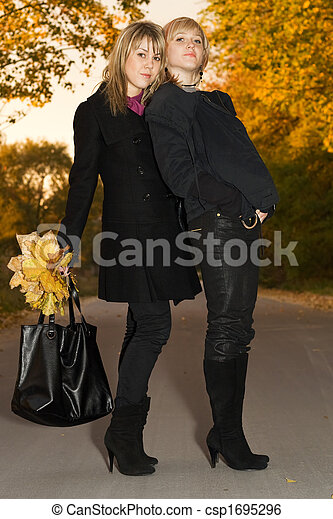 Two young blondes with autumn leaves on a road - csp1695296