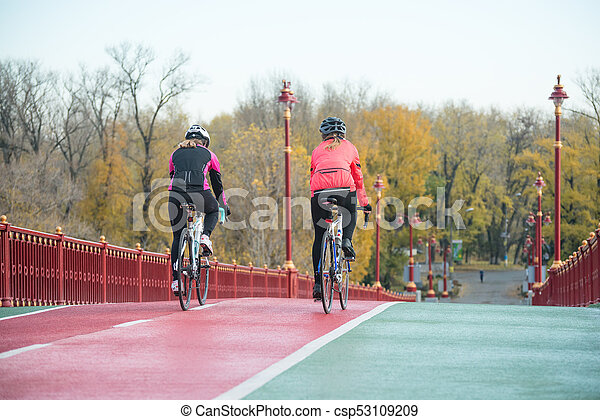 Two Young Female Cyclists Riding Road Bicycles on Bridge Bike Line in Cold Autumn Day. Healthy Lifestyle Concept. - csp53109209