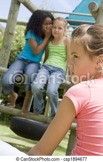 Two young girl friends at a playground whispering about other gi - csp1894677