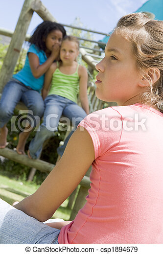 Two young girl friends at a playground whispering about other gi - csp1894679