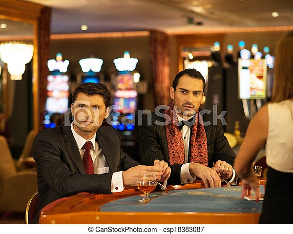 Two young men in suits behind gambling table in a casino - csp18383087