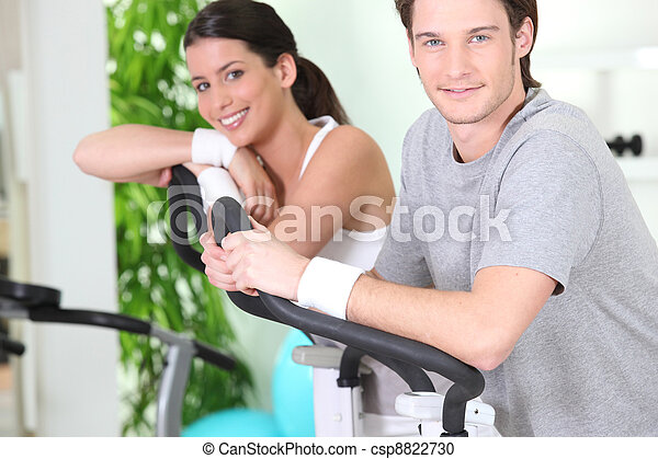 two young people resting on cardio machines - csp8822730