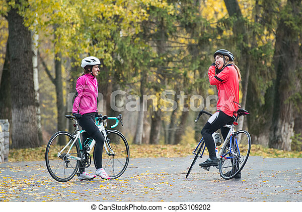 Two Young Smiling Female Cyclists with Road Bicycles Resting and in Park in Cold Autumn Day. Healthy Lifestyle. - csp53109202